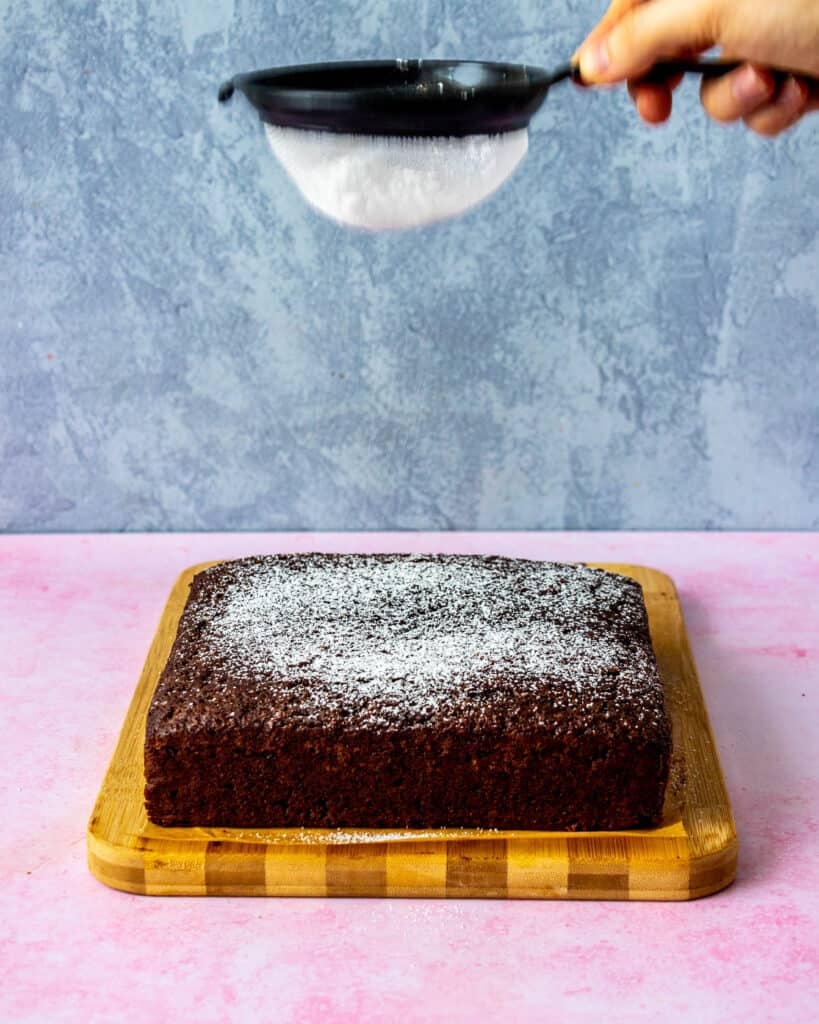 dusting confectioners sugar on top of cake