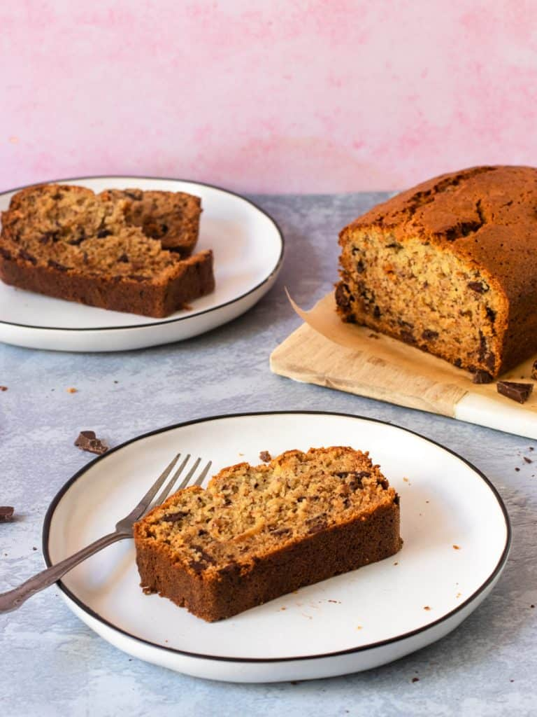 Gluten Free Chocolate Chip Banana Bread slice on a plate with loaf in background