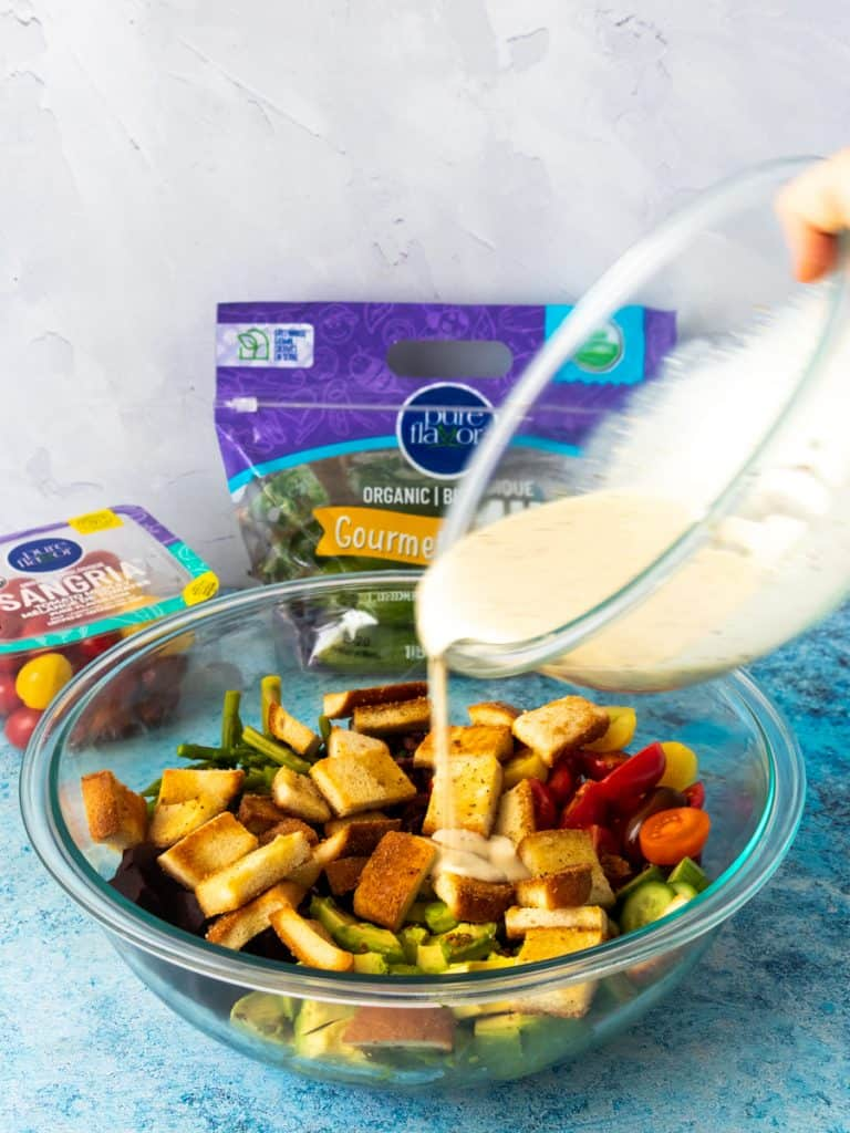 pouring dressing over Gluten Free Greek-Style Panzanella Salad