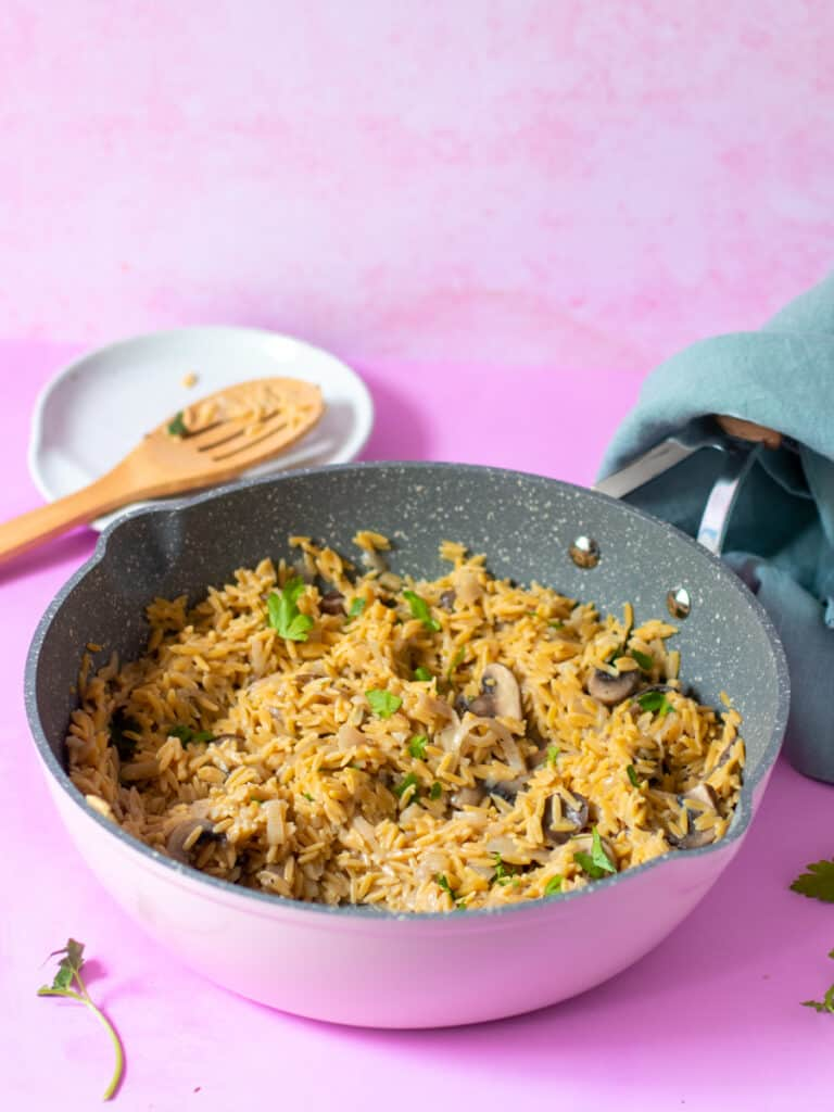 Gluten Free Orzo in frying pan with towel on pink background