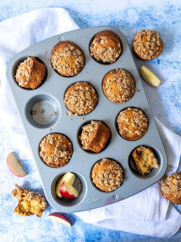 gluten free apple muffins in muffin pan with white towel