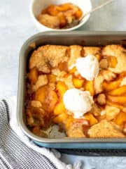 gluten free peach cobbler in pan with ice cream